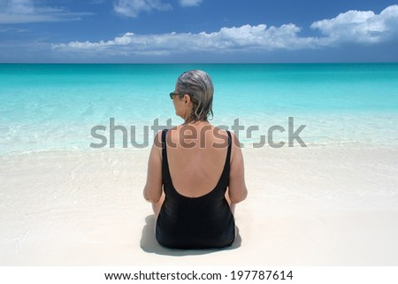 mature woman sits at water's edge on a pristine beach in the Turks and Caicos Islands - stock photo