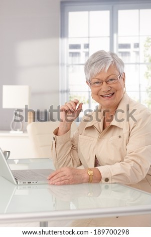 Mature woman sitting at home, using laptop computer, smiling happy. - stock photo