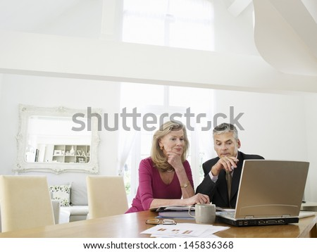 Mature woman sitting at table with financial advisor - stock photo