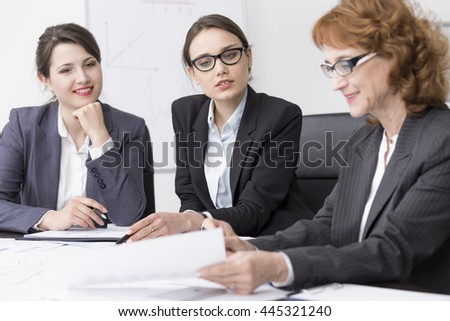 Mature woman sitting beside desk talking with two young businesswomen - stock photo