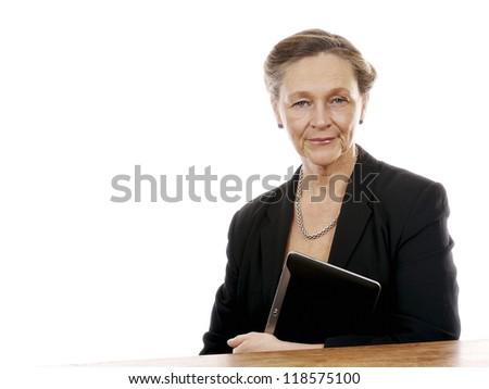 Mature woman sitting by table working on tablet computer isolated on white background