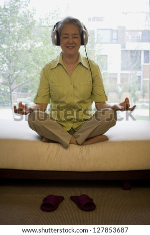 Mature woman sitting cross legged meditating with headphones smiling