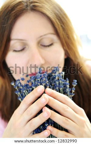 Mature woman smelling lavender flowers - focus on hands - stock photo