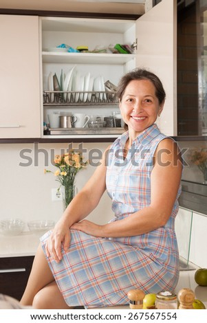 Mature woman smiling at her big kitchen - stock photo