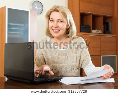 mature woman staring financial documents at table in home interior