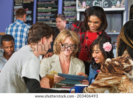 Mature woman studying with friends in coffee house