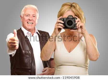 Mature Woman Taking Photograph In Front Of Man Gesturing On Gray Background - stock photo