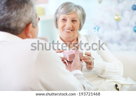 Mature woman taking small pink giftbox from her husband hands - stock photo