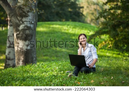 Mature woman talking on smart-phone holding a laptop sitting on the grass in the park