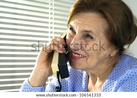 Mature woman talking on the phone on a light background