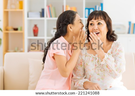 Mature woman telling a secret to her surprised friend - stock photo