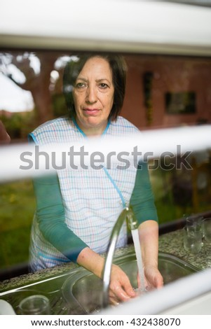 Mature woman through a glass, she is washing dishes.