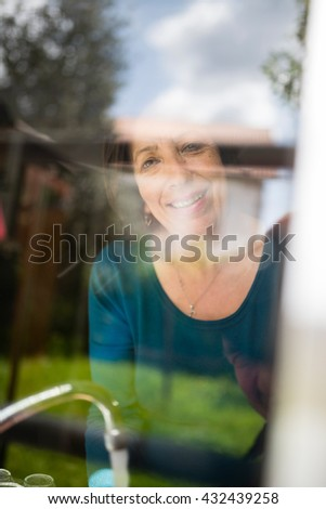 Mature woman through a glass, she is washing dishes, Spain.