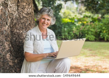 Mature woman using a laptop sitting on tree trunk smiling at camera in park