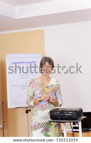 Mature woman using a projector in a presentation as she stands in front of the flipchart with a lovely friendly smile - stock photo
