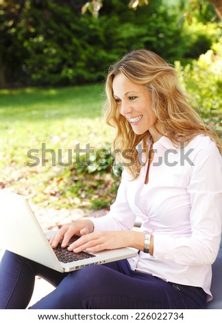 Mature woman using her laptop while sitting at home at garden.  - stock photo