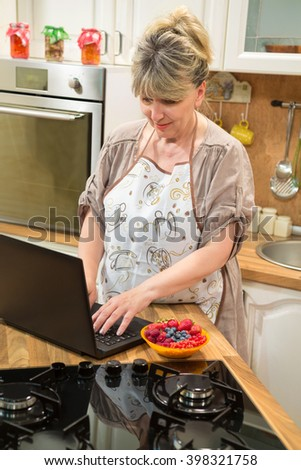 Mature woman using laptop in the kitchen and searching recipe on the internet.