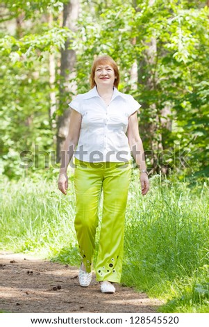 Mature woman walking in forest - stock photo