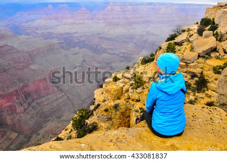 Mature woman watching a storm filled sunset on the south rim of the grand canyon