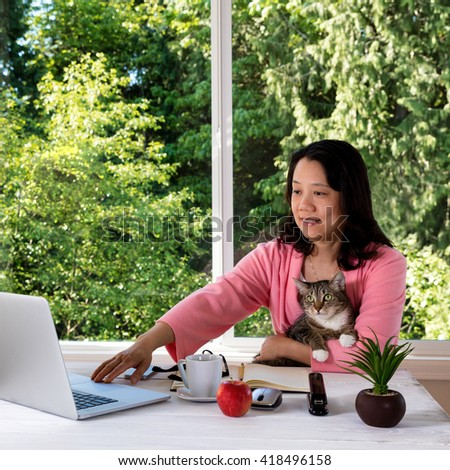 Mature woman, wearing morning attire, holding her family pet cat while working from home in front of large window with bright daylight and trees in background.  - stock photo