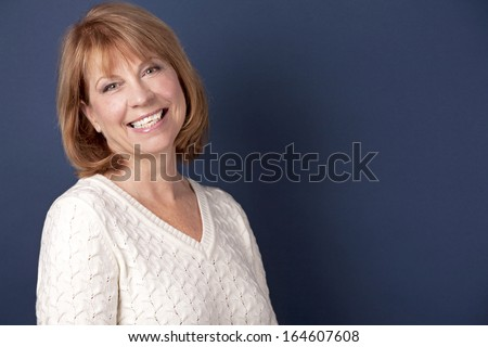 mature woman wearing white sweather on dark blue background - stock photo