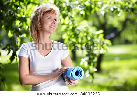 Mature woman with a gym mat in the park - stock photo