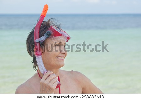 mature woman with a mask for snorkeling in the sea background - stock photo