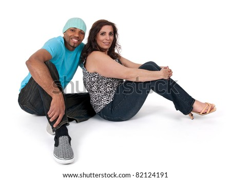 Mature woman with a young guy, sitting close to each other and smiling. - stock photo
