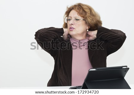 Mature woman with closed eyes sitting at the tablet and touching her neck.  - stock photo