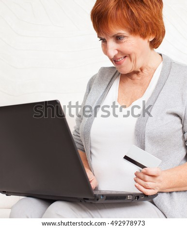 Mature woman with credit card looking at the laptop. Female is shopping via Internet