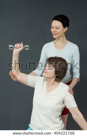 Mature woman with dumbbells and young coach of gymnastics. Woman with fitness dumbbells. Old woman is smiling in the studio. Mellow woman do her exercises and smile.  - stock photo