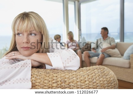Mature woman with family in background at home