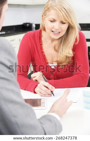 Mature Woman With Financial Advisor Signing Document At Home - stock photo