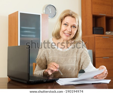 mature woman with financial documents at table in home or office interior