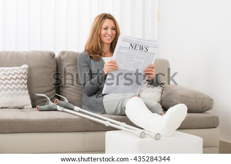 Mature Woman With Fractured Leg Reading Newspaper In House - stock photo