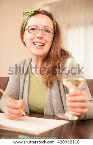 Mature woman with glasses, coloring and drinking white wine