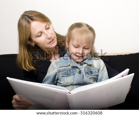 mature woman with granddaughter reading book at home, happy family together - stock photo
