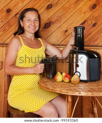 Mature woman with juicer machine, adding  pear and smiling - stock photo