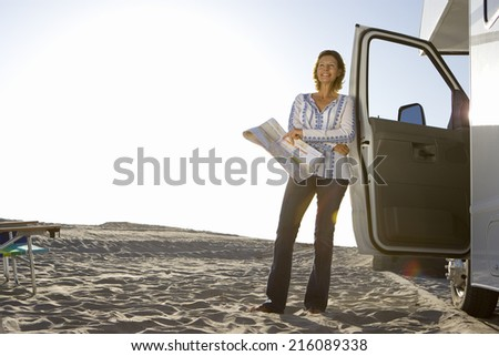 Mature woman with map by motor home on beach, smiling, low angle view (lens flare) - stock photo