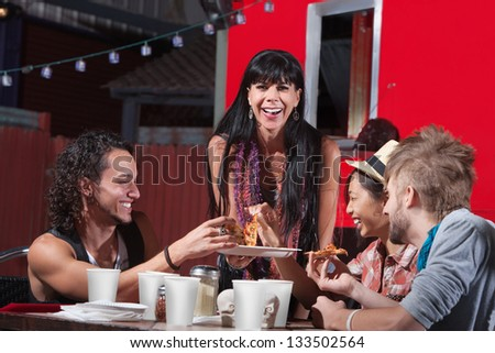 Mature woman with younger group eating pizza - stock photo