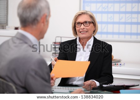 Mature woman working at her desk - stock photo
