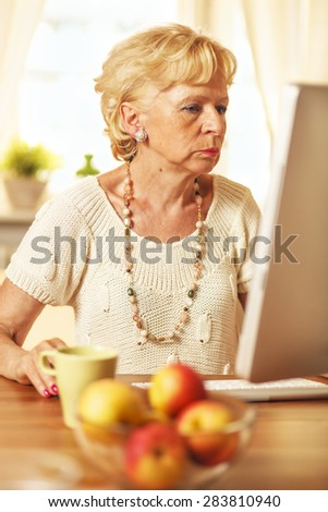 Mature woman working on apple computer, at home