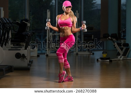 Mature Woman Working Out Biceps In Fitness Center - Dumbbell Concentration Curls - stock photo