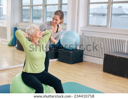 Mature woman working out on a fitness ball with help from personal trainer at gym. Happy senior woman exercising with female instructor at health club.