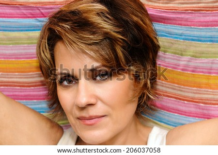 Mature Woman wrapped up in colorful fabric - stock photo