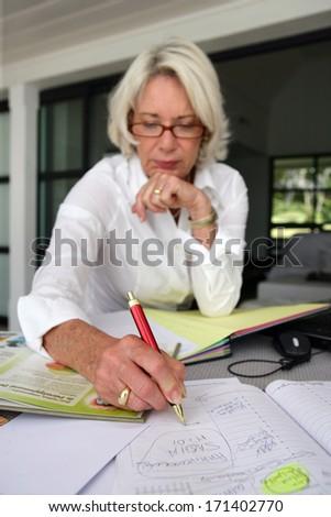 Mature woman writing - stock photo