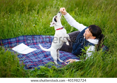 Mature woman 35-40 years old playing with her dog Jack Russell Terrier on nature in summer evening. Focus on woman face - stock photo