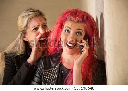 Mature woman yelling to ear of teenager on phone - stock photo