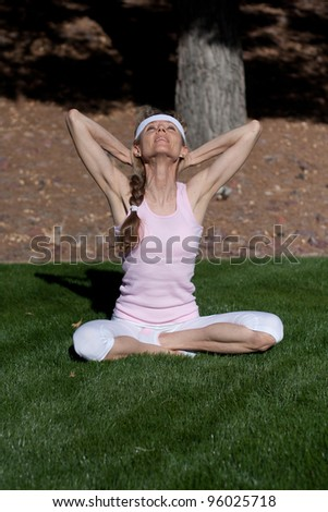 mature women exercising on grass in park - stock photo