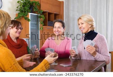 Mature women having fun with pack of cards indoor  - stock photo